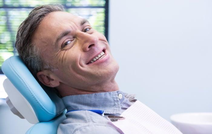 man smiling dental chair